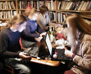 Four people, concentrating on their laptops, in a library
