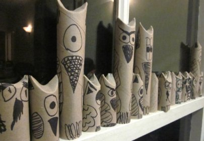 Cardboard tubes painted to look like owls, lined up on a window sill.