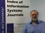 "John Lamp, standing in front of a banner saying ""Index of Information Systems Journals"