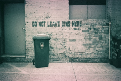 A bleak image of a No Parking space, with a sign that says 'Do not leave bins here'. There is a bin directly under the sign.