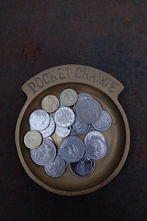 A brass tray holding Australian coins. At the top of the tray is engraved 'Pocket change'.