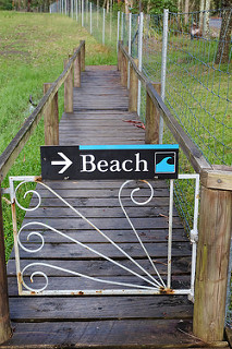 "Sign on a small gate says ""Beach"", with an arrow. Beyond the gate is a wooden walkway into the distance."