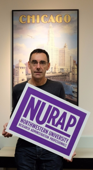 Jonathan looking nervous, as he holds a NURAP sign in front of a poster that says 'Chicago'