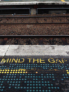 Text on a railway platform that says 'mind the gap'.