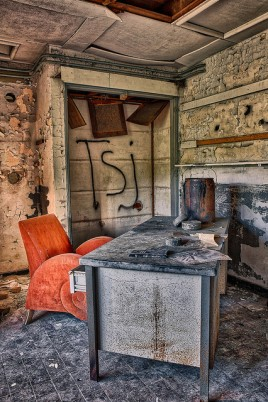Urbex image of an old and abandoned desk, with a bright orange chair behind it. On the wall is graffiti - TSJ