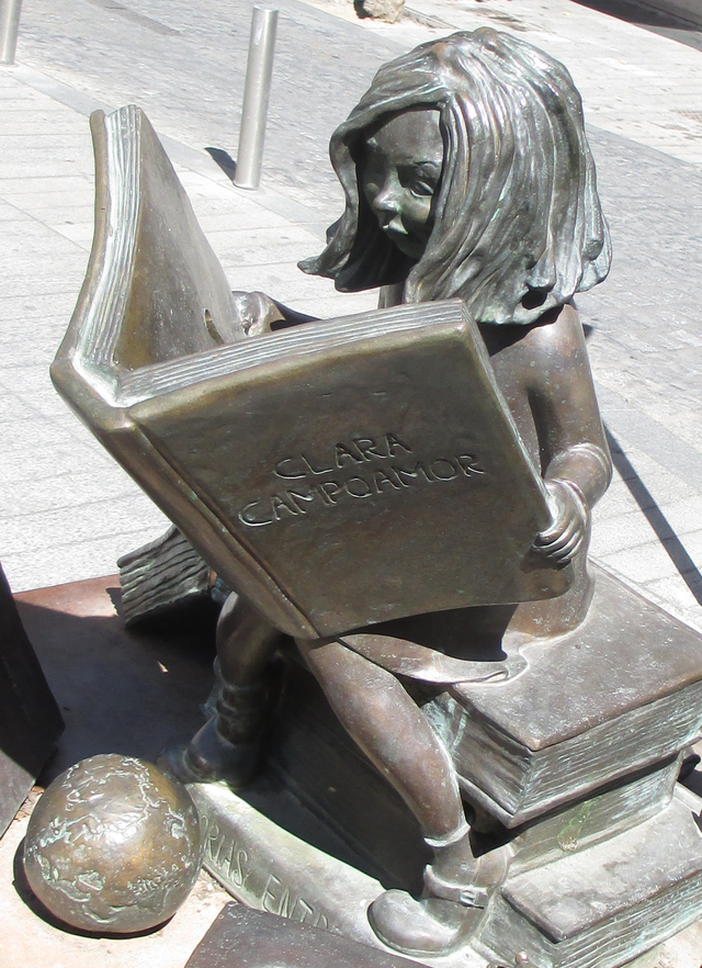 An statue of Clara Campoamor as a little girl, sitting on books and reading a big book with her name on it.