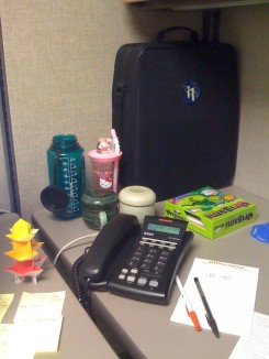 A cubicle corner, showing office stationery and a desk phone.