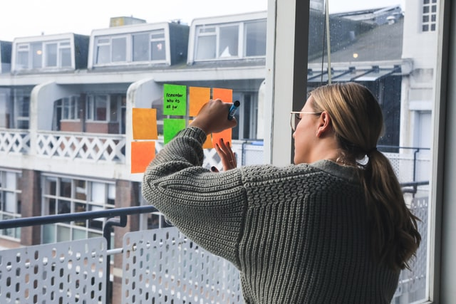 A woman writing on post-it notes stuck on the window of her apartment