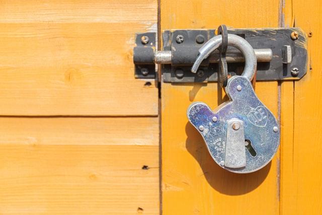An open padlock, hanging on a door.